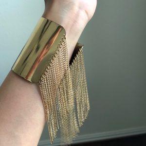 Gold wrist bangle with fringes.